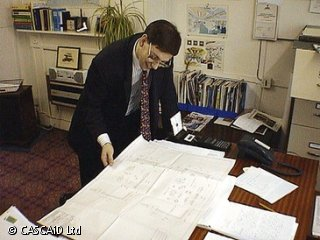A man, wearing a suit and tie, is standing by a large table in an office.  He is looking at a large paper plan, which is lying open on the table.