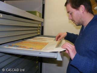A man is studying a colourful geological map, which is laid out on a metal drawer in front of him.