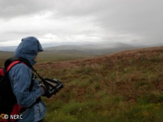 A woman is standing on a hillside in bad weather.  She is typing into a tablet computer.