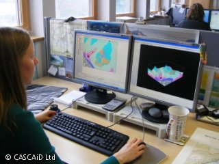 A woman is sitting in front of two computer monitors which are displaying colourful geological maps.