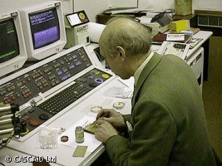 A man is sitting at a desk, with a control panel and computer screens.  He is performing an experiment.
