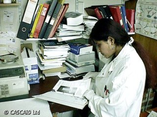A woman, wearing a white lab coat, is sitting at a desk, looking at a folder.