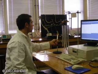 A man in a white lab coat is sitting at a desk.  He is about to strike some metal wind chimes with a metal instrument.  There is a computer on the desk in front of him.