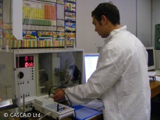 A man in a white lab coat is standing in front of a large piece of scientific equipment.