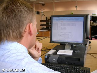 A man is sitting at a desk, using a computer.  There is a spreadsheet on the computer screen with figures and a small graph.