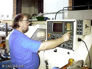 A man is standing next to the control panel of a large machine.  He is pressing a button on the panel.
