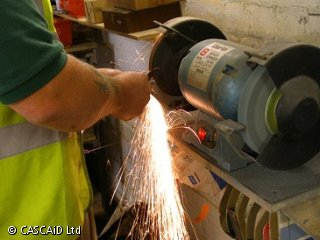 A man is using a grinding machine in order to grind down a metal object.  Sparks are shooting out from the grinding wheel.  The man is wearing a yellow tabard.