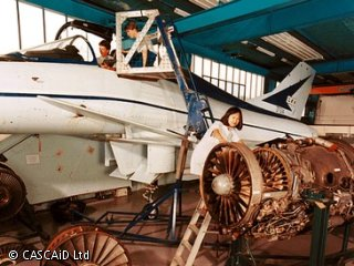 An aeroplane is parked inside a large workshop.  An aeroplane engine is on the floor beside the aircraft and a woman is looking at it.  Two people are in the cockpit area of the aircraft.