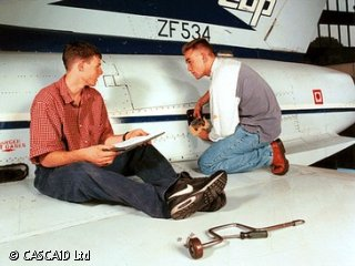 Two men are sitting on the wing of a jet aircraft.  They are talking and looking at a clipboard.  There is a piece of metal equipment beside them.