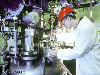 A man, wearing a white lab coat, red hard hat and protective goggles, is using a large piece of scientific equipment to check the levels of a particular chemical.