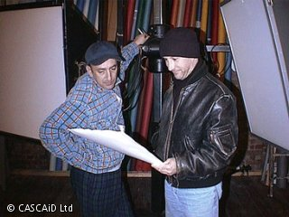 Two men are talking and looking at a sheet of paper.  They are standing next to some studio lighting equipment, inside a room.
