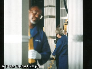 Two people are inspecting various, long metal pillars.  They are wearing blue lab coats.