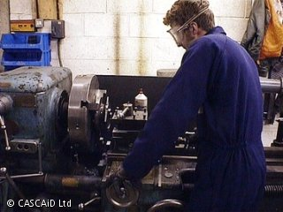 A man, wearing blue overalls and safety goggles, is using a large grinding machine in a workshop.