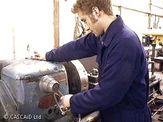 A man, wearing blue overalls, is using a large machine, in a busy workshop.  He is setting the speed of the machine.