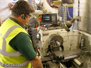 A man, wearing a yellow, reflective tabard and safety goggles, is standing in a workshop.  He is using a lathe to produce a machine tool.