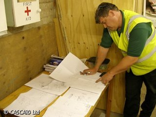 A man, wearing a yellow, reflective tabard, is standing next to a table.  He is looking at some sheets of paper, which are laid out on the table.  They have technical drawings on them.