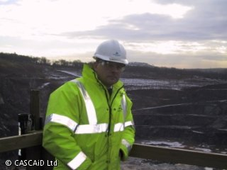 A man, wearing a high visibility jacket and a hard hat, is standing on a platform, overlooking a quarry.