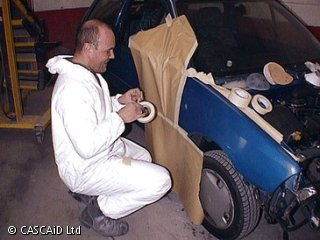 A man, wearing a white protective suit, is crouched down next to a blue car.  He is covering parts of the car with paper using tape, to protect it from spray paint.