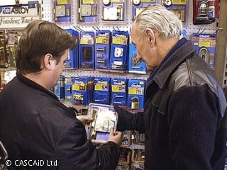 Two men are standing in a shop looking at various security products displayed, hanging on the shop wall.