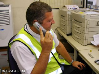 A man, wearing a yellow tabard, is sitting at a desk, speaking on a telephone.