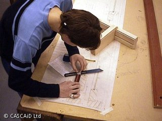 A man is standing at a workbench.  He is drawing on a large sheet of paper.