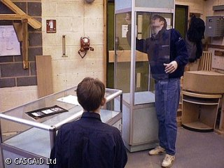 Two men, wearing blue overalls, are standing in a room, assembling glass display cabinets.