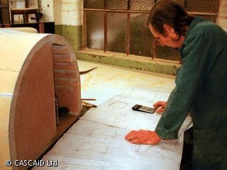 A man, wearing overalls, is standing in a workshop.  He is looking at a large sheet of paper.