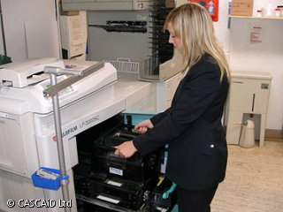 A woman is standing by a large machine.  She is filling various trays inside the machine, with paper.