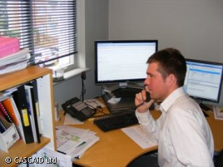 A man is in an office talking on the phone.  There are two computer screens on his desk.