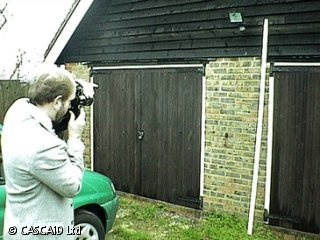 A man is standing in a garden.  He is taking a photograph of a garage.