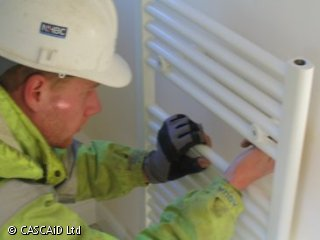 A man in a high visibility vest and white hard hat is fixing a radiator to the wall.