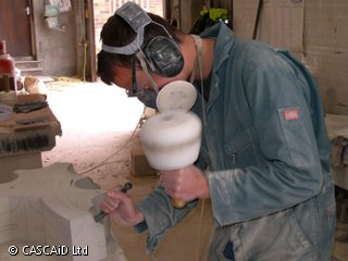 A man, wearing a boiler suit, protective goggles and a mouth mask, is standing in a workshop.  He is using a mallet and a chisel on a block of stone.