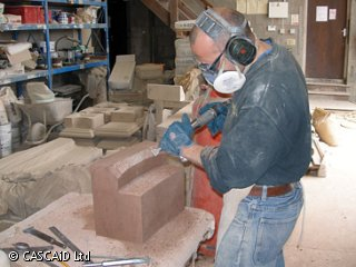 A man, wearing a boiler suit, protective goggles and a mouth mask, is standing in a workshop.  He is using an electric chisel on a block of stone.