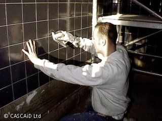 A man is crouching next to a wall.  He is fitting black tiles to the wall.