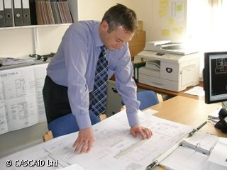 A man is standing at a desk, in an office.  He is looking at various paper documents.