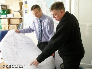Two men are standing in an office.  They are looking at a large sheet of paper.