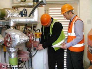 Two men, wearing hard hats and high visibility tabards, are looking at a series of pipes on a wall.