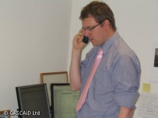 A man wearing a blue shirt with a pink tie is talking on a cordless phone.