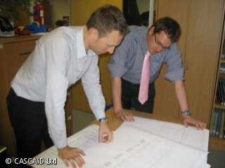 Two men are standing looking at some plans.  One man is wearing a blue shirt with pink tie.  The other man is wearing a white shirt.