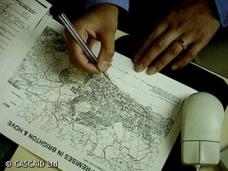 A man is sitting at a desk, looking at a small map.