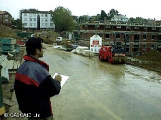 A man is standing on a large building site.  He is making notes on a notepad.