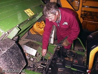 A man, wearing a boiler suit, is fixing the engine of a piece of horticultural machinery.