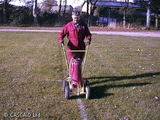 A man, wearing a boiler suit, is marking white lines on a football pitch.
