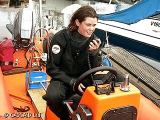 A woman, wearing a wet suit, is sitting at the controls of a small boat.  She is speaking on a radio.