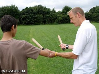 A man is holding a rounders bat in his right hand.  With his left hand, he is showing a student how to hold a bat.