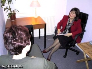 Two women are sitting in chairs, facing each other and talking.  One of the women is holding a notepad.