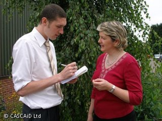 A man is talking to a woman.  They are standing outside, next to a tree.  The man is making notes on a notepad.
