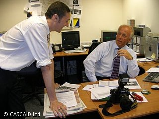 A man is sitting at a desk.  He is talking to a man who is standing, leaning on the desk.  There are paper documents and a camera on the desk.