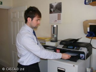 A man is standing by a printer in an office.  He is about to take a printed sheet out of the printer.