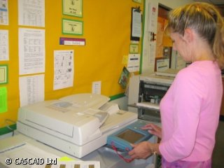 A woman is pressing buttons on a photocopier.  There are notices attached to the wall behind the photocopier.